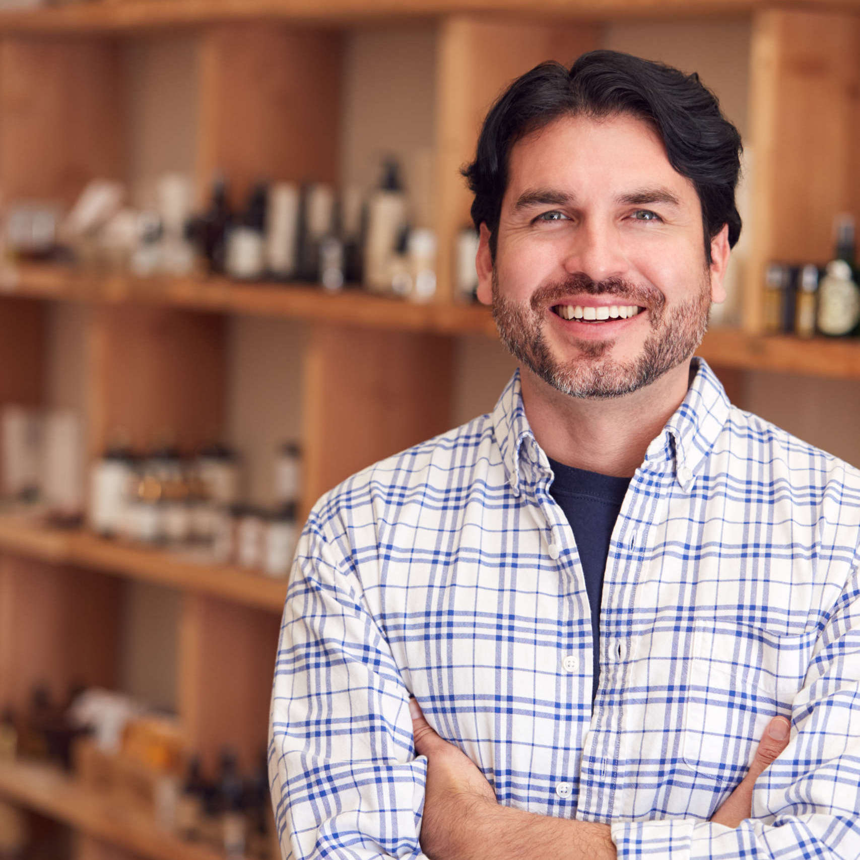 Portrait Of Male Owner Of Gift Store Standing In Front Of Shelves With Cosmetics And Candles